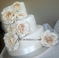 Three tier fondant modern unique wedding cake design with silk roses and ribbons