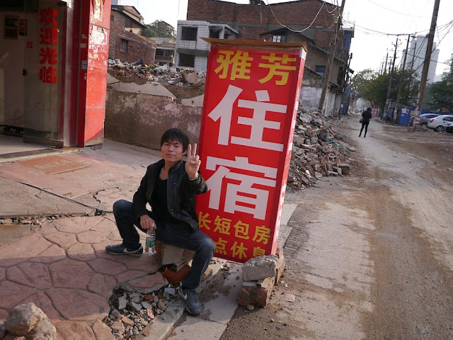 man sitting in front of a motel sign at Beizheng Street in Changsha