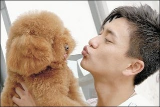 Bosco Wong making kissy faces at a dog