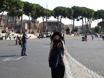 Lisa in a black dress, expansive black furry (fake) hat, and a dark blue Uruguayan bag, in the centerline of the Fori Imperiali road.