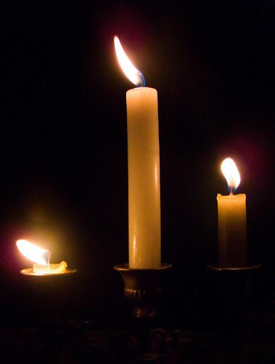 Foto de tres velas encendidas en un candelabro