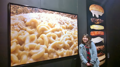 Photo of me between two Modernist Cuisine exhibit photos at Pacific Science Center: Mac and Cheese by Chris Hoover 2011 and Levitating Hamburger by Ryan Matthew Smith 2009