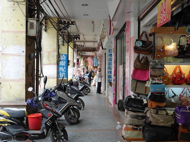buildings overhanging a sidewalk with motorbikes and bags for sale in Yangjiang, China