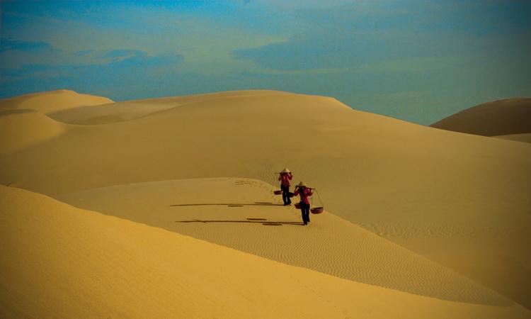 Ảnh 2 cô gái gánh hàng qua bãi cát vàng