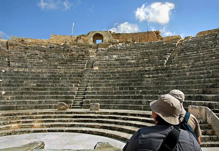 Vista sobre a zona das bancadas do Anfiteatro de Dougga. Duas pessoas sobre a direita