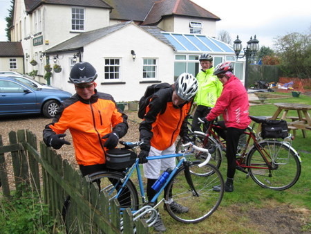 Cyclists look at bike stuck in fence