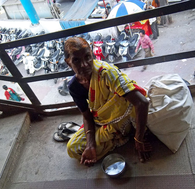 elderly woman beggar on railway bridge