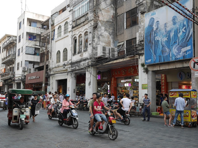 "motorbikes, an auto-rickshaw, a food stall, pedestrians and an advertisement for PEAK NBA products with the words ""I can play"" on Xinhua Road in Haikou"