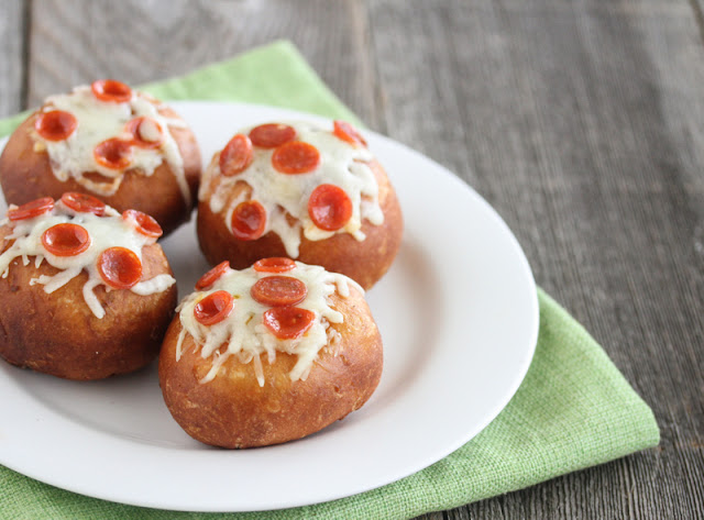 a close-up shot of four pizza donuts on a white plate with a green napkin underneath