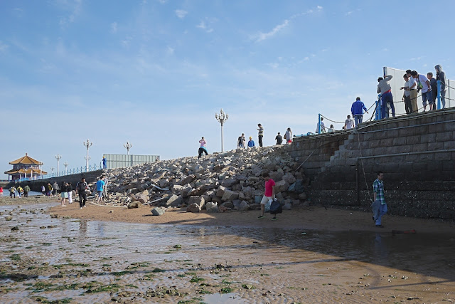 people climbing over a collapsed portion of a pier
