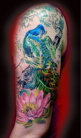 Colorful peacock and lily tattoo on arm