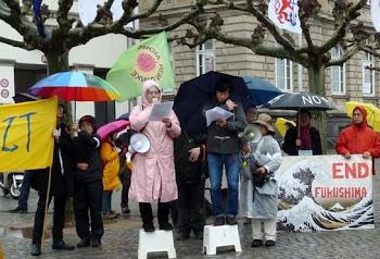 Kundgebung im Regen mit bunten Schirmen, Fahnen und Transparenten.