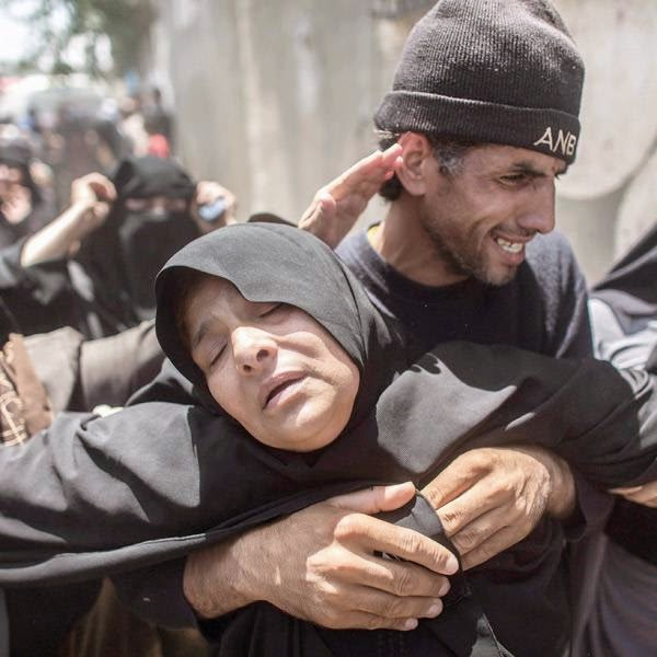A female member of the Sheik el Eed family faints during the funeral of her two sons and granddaughter outside Rafah, southern Gaza Strip.