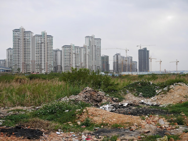 new apartment complexes being built behind an empty lot in Yangjiang, China