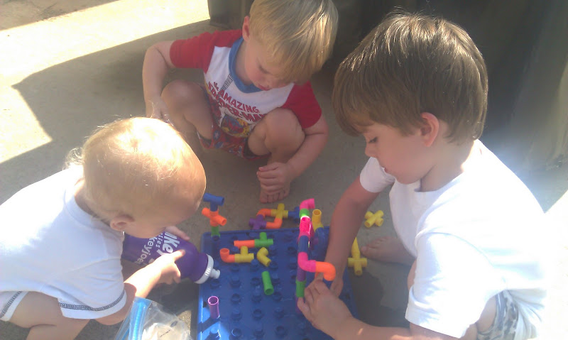 The boys playing with plastic pipes and water.