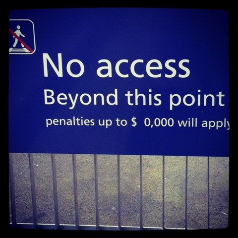 "A sign which reads: ""No Access Beyond This Point, penalties up to $0,000 will apply."""
