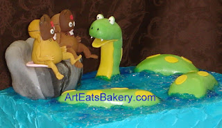 The Green Anaconda Song custom designed kid's birthday cake with two sugar sculpture rats, rock and snake on blue sugar water