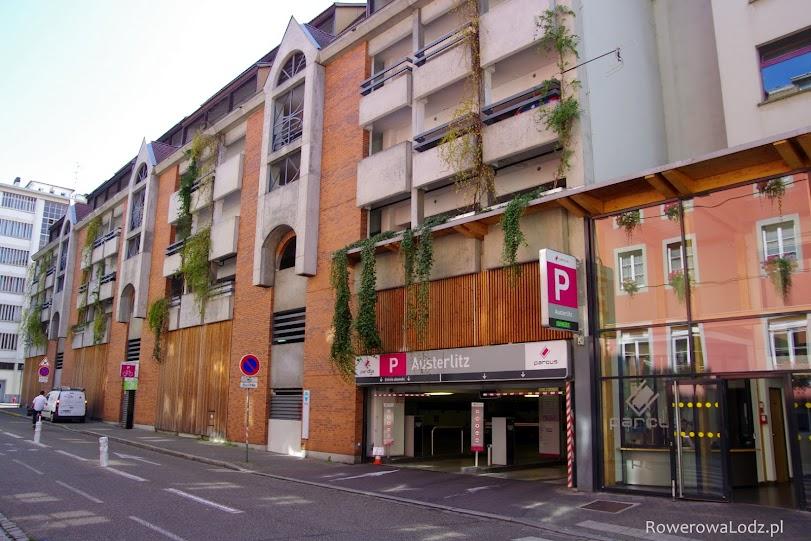 Po lewej piętrowy parking samochodowy, po prawej parking rowerowy.