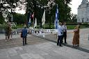 photo: quatre personnes discutent ensemble, derrière eux un drapeau du Québec et la façade de l'Assemblée nationale