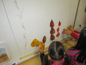 Children tape leaves to a wall to make a graph by leaf shape.