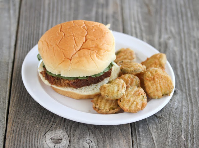 photo of a burger with a side of fried pickles