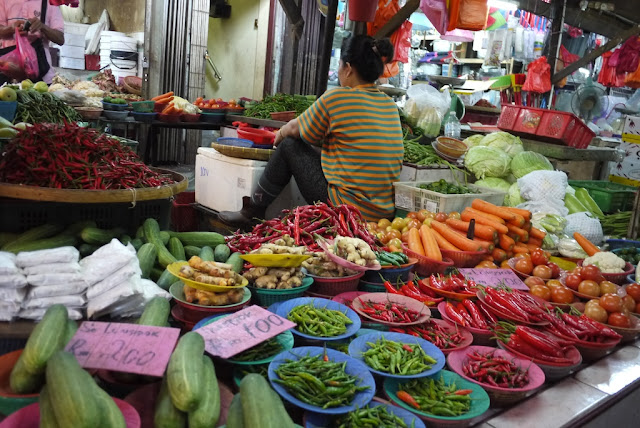 woman sitting next to vegetables for sale at Bazaar Baru Chow Kit in Kuala Lumpur, Malaysia