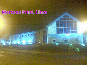 Sodium streetlit view of the dark church like glass frontage and offices of Mortons Print Media