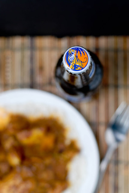 A close up of a plate of food on a table, with Tiger Beer