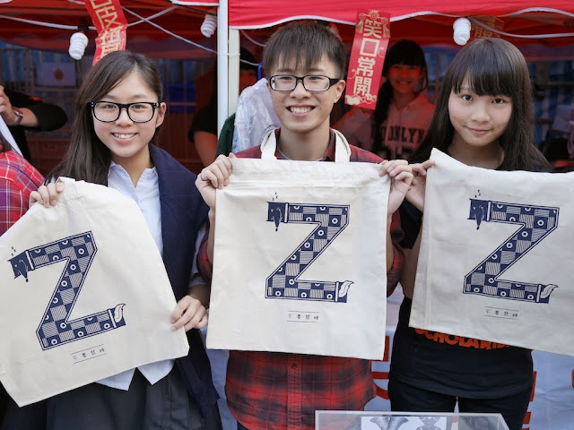 "three college students holding bags with a large letter ""Z"""