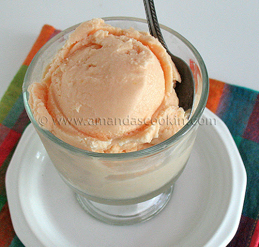 A close up photo of orange ice cream in a clear dish.