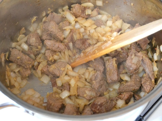 onion and ginger added to pot of cooked meat