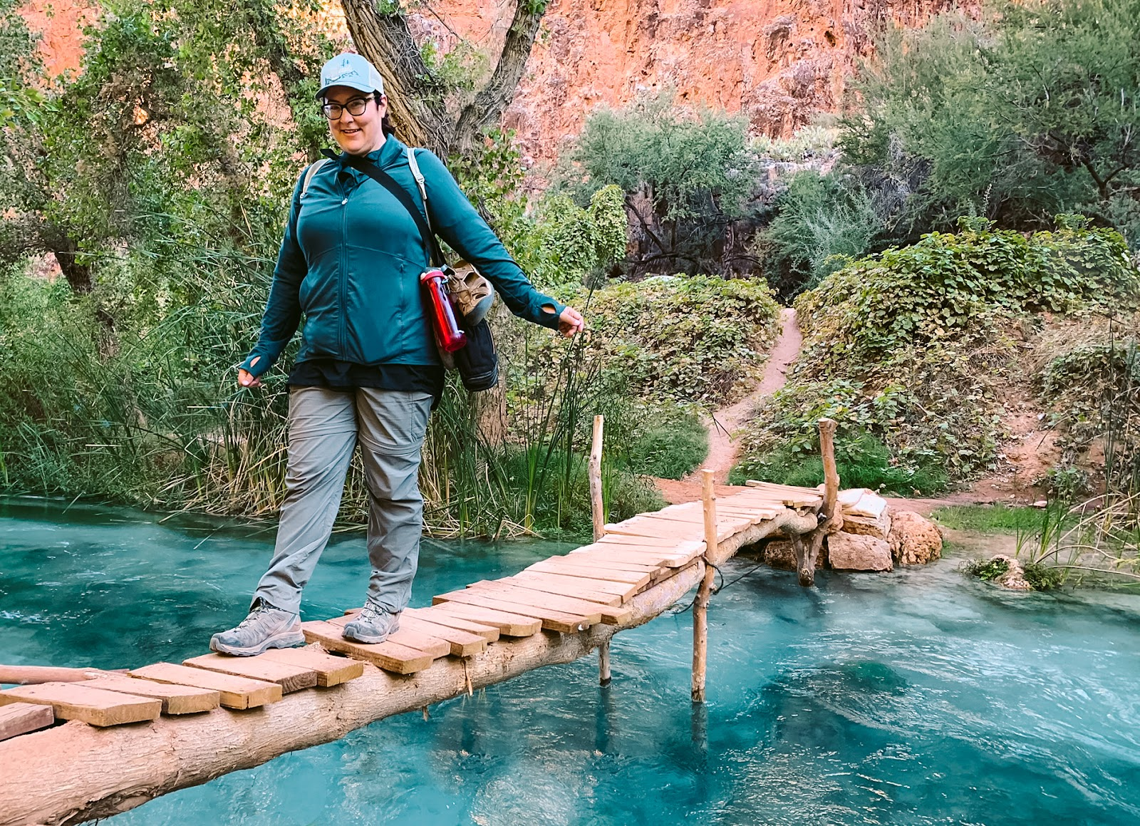 A female hiker crosses a bridge over a deep blue stream in an orange canyon.  Another hike like this is part of my 2021 goals.
