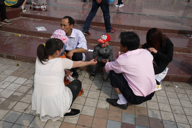 family sitting and squatting at Nanmen Square in Yinchuan, Ningxia, China
