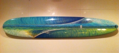 A 9'6 with 3 stringers in the waves. Hand painted and shaped out of a Clark Foam blank