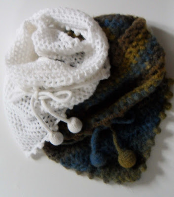 Two Wrap crochet scarves. One is white the other is tan through to blue. They both have a loose crochet stitch and are tied around you with cords which end in pompoms.