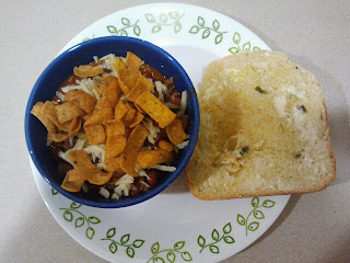 Taco soup topped with sour cream, shredded cheese and Frito's