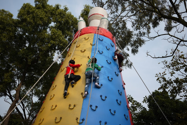 Three children climbing an inflatable climbing pylon at an amusement park ride in Zhuhai, China