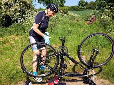 Woman wearing rubber gloves examines upturned bike