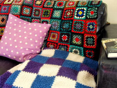 couch, knitted throw and a copy of Doll Bones by Holly Black