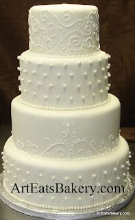 Four tier elegant white fondant wedding cake with royal  icing curlicue scrolls diamond and pearls design