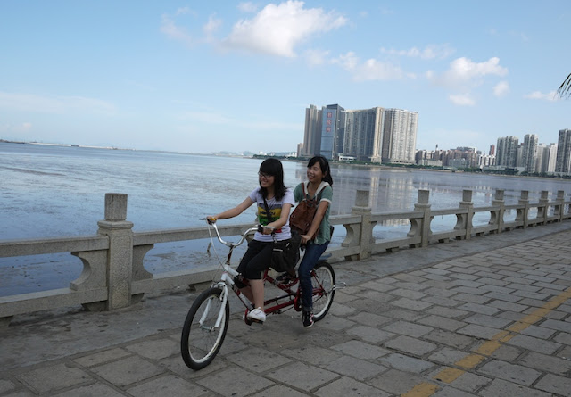 two young women riding a tandem bicycle in Zhuhai, Guangdong province