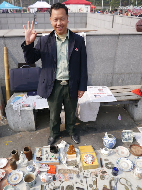 man with his items for sale at an outdoor antique market in Changsha