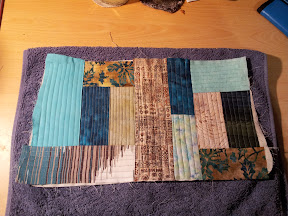 A scrappy patchwork quilted (quilt-as-you-go) bag piece