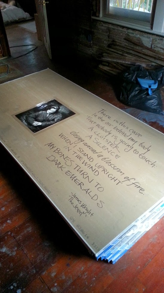 A piece of Sheetrock with a large portrait photograph of DarkEmeralds taped to it, and the poem The Jewel by James Wright