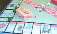 Unique Monopoly board game birthday cake with edible houses, hotels, money, dice, and silver playing pieces 3