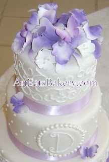 Three tier unique white fondant wedding cake with monogram, curlicue design, purple flowers, buttterflies closeup