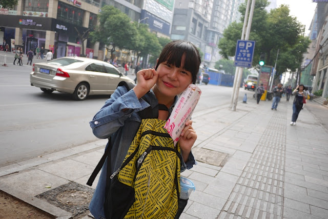 female college student handing out small advertisement fliers in Changsha, China