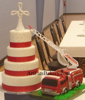 4 Tier white fondant wedding cake with silver pearls, red ribbons and 3D fire truck groom's cake with the ladder going up to the wedding cake