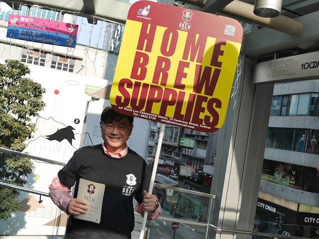 "man wearing HK Brewcraft shirt holding sign reading ""Home Brew Supplies"""