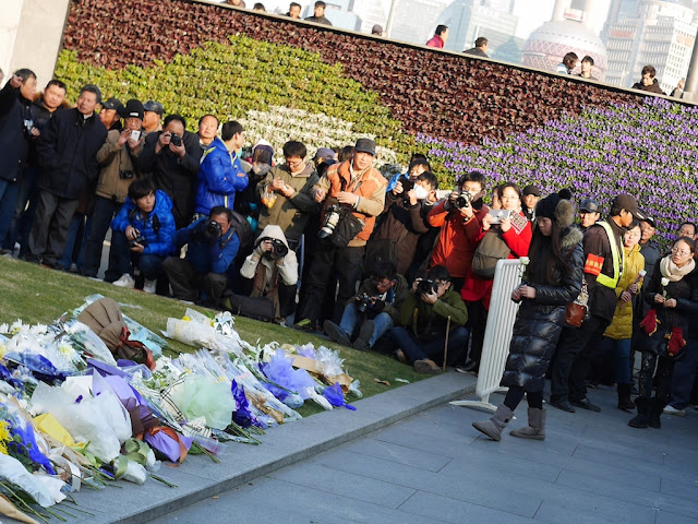 young woman bring a flower to a memorial for people killed and injured by the New Year's Eve stampede in Shanghai